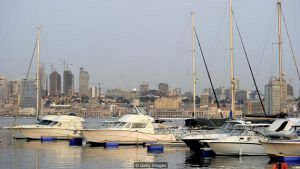 Boats are docked in a marina with Luanda